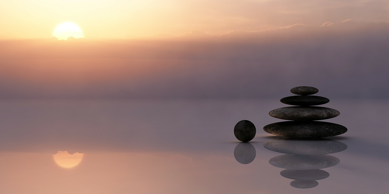 Three stacked rocks and a circle rock sitting beside them